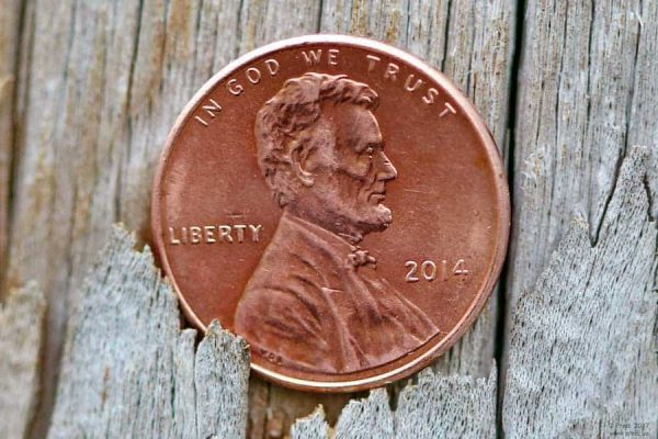 A penny falling through the cracks of a wooden floor, with Abe Lincoln's face up
