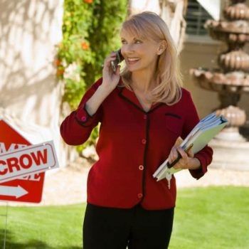 First Time Home Buyer Myths - Real Estate agent standing in front of a house in escrow sign.