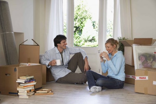 A couple enjoys a coffee break before finishing up their packing for a move.