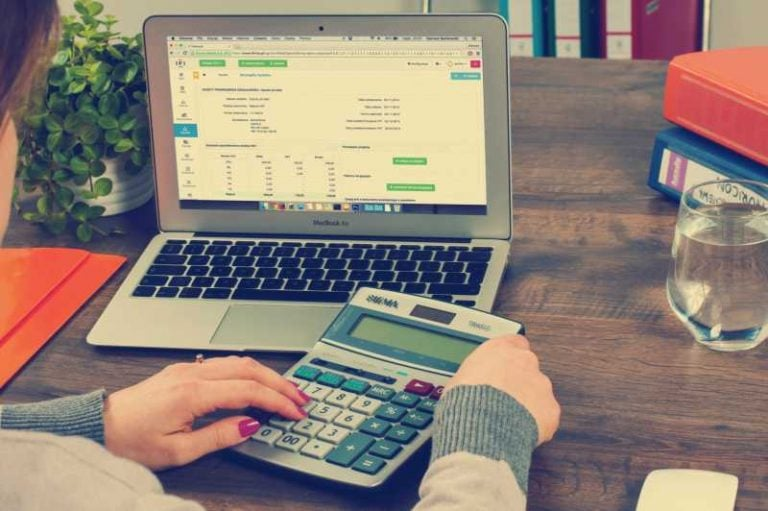 Woman using calculator and laptop to find savings on San Marcos real estate