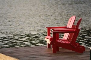 Red lawn chairs on deck overlooking lake