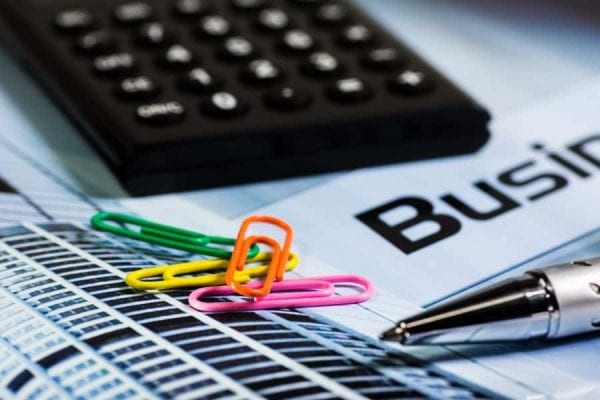 Colorful paperclips on paperwork beside calculator