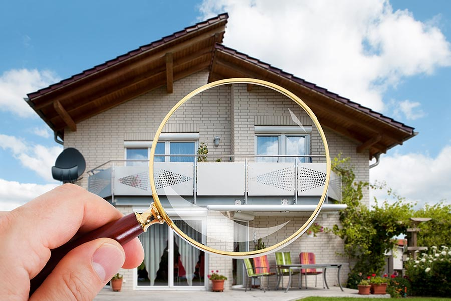 Man inspecting a house with magnifying glass