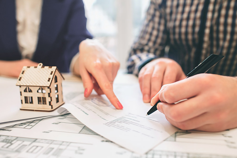 Man Signing a contract for a house