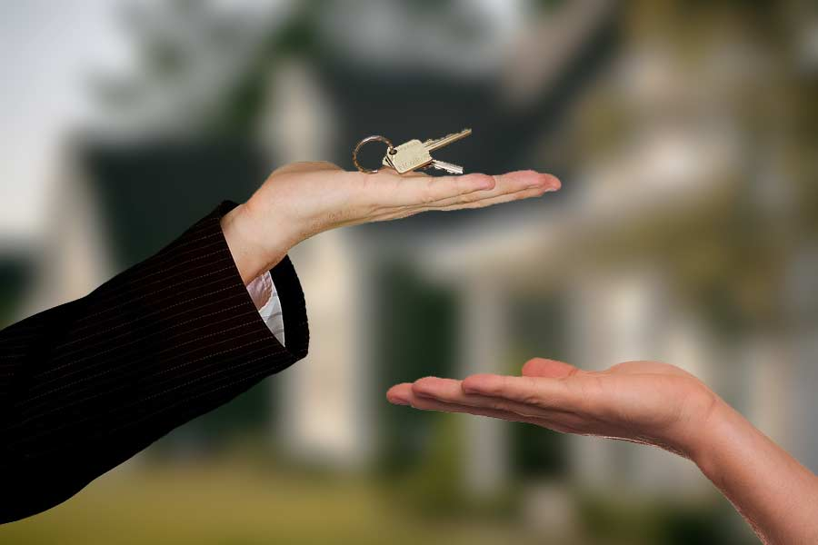 Hands holding a set of house keys just out of reach