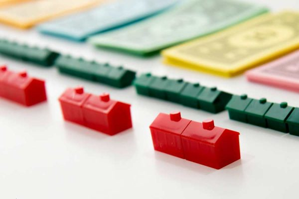Monopoly houses and money laid out in a row