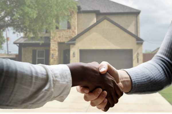 Handshake with real estate agent in front of home