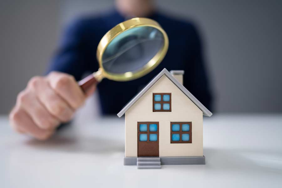 Magnifying glass held to a toy model of a house
