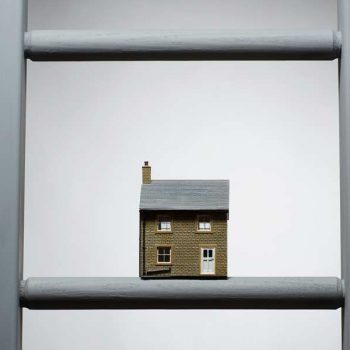model of a house on a ladder rung
