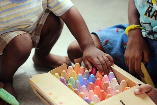 children playing with chalk on a driveway